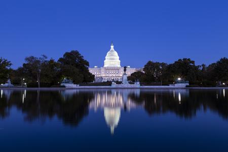 プールの反映ライトで照らされた夕暮れ時にアメリカ合衆国議会議事堂