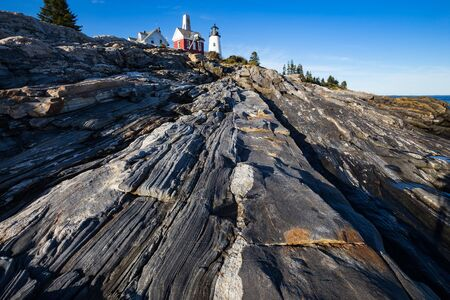 striated: Pemaquid Point Lighthouse above rocky coastal rock formations on the Atlantic coast of Maine Stock Photo