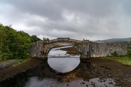 Garron Bridge over the Gearr Abhainn river near Inveraray, Highlands Scotland, on a cloudy and rainy day