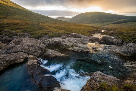 A waterfall cascade at the Fairy Pools with the Cuillin mountains