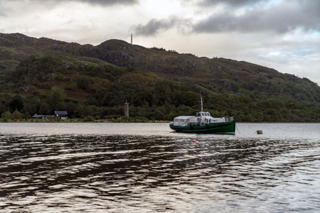 Fisher boot on Loch Shiel lake with Glenfinnan Monument in the background. Highlands Scotland Uk 写真素材