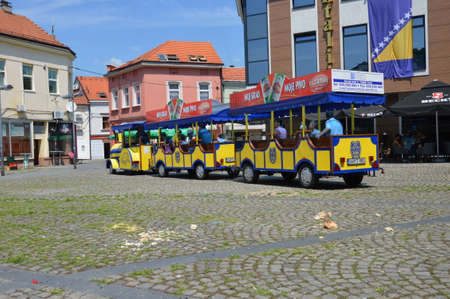 Tourist train with tourist who want  to look at and visitor Pannonian lake goes the square freedom in city Tuzla Editorial