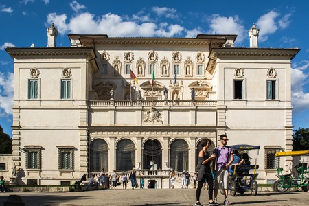 villa borghese: Rome, Italy - June 21, 2014: the entrance of the Galleria Borghese in Villa Borghese where citizens and tourists strolling in the park on a sunny Sunday afternoon. Some tourists use the rishock to stroll along the avenues of the villa.