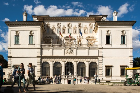 place of interest: Rome, Italy - June 21, 2014: the entrance of the Galleria Borghese in Villa Borghese where citizens and tourists strolling in the park on a sunny Sunday afternoon. Some tourists use the rishock to stroll along the avenues of the villa.