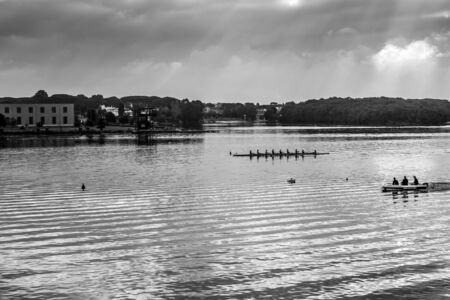 sports shell: Sabaudia, Italy - April 18, 2015: a rowing team performs a morning workout in the lake of Paola. Lake Paola also called Laguna Sabaudia or Sabaudia lake is a brackish lake in the coastal provinces of Latina in the Circeo National Park