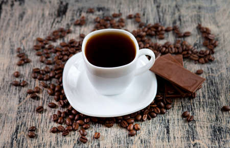 invigorating: Aromatic invigorating cup of black coffee powder, chocolate and coffee beans scattered on the table Stock Photo
