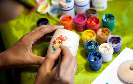 The artist paints with bright colors