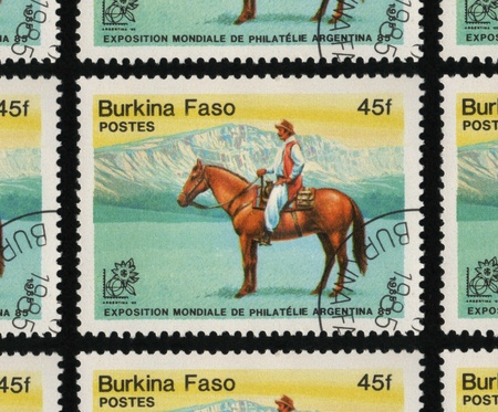 franked: BURKINA FASO - CIRCA 1985: A used postage stamp printed in Burkina Faso from the International Stamp Exhibition Argentina 85 - Buenos Aires - Horses issue, showing a man riding a horse.