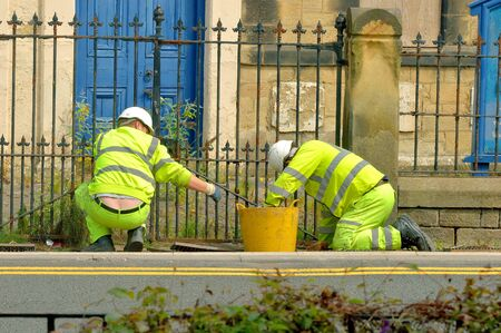 drains: Two council workers cleaning drains outside iron church gates. Stock Photo