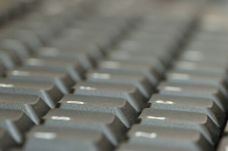 acute angle: Computer keyboard. Close up of mostly blurred bands of keys on an acute angle.
