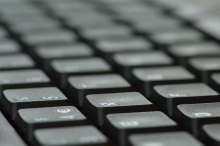 Computer keyboard. Close up of mostly blurred bands of keys on an angle.