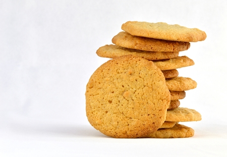 staggered: Staggered stack of homemade peanut butter cookies with one resting against it. On a white background. Stock Photo