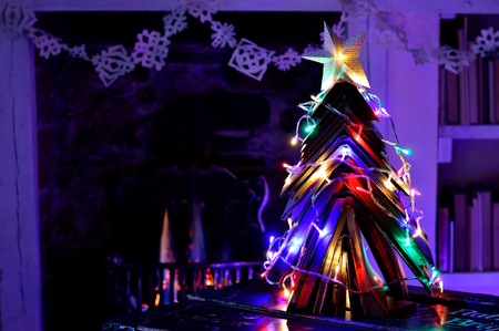 Christmas tree made from vintage books with fairy lights in front of an open flame fire. With star and snowflake chain made from book pages. 免版税图像