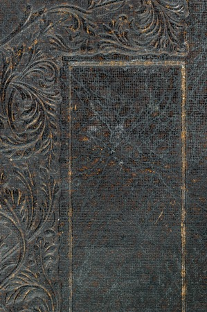 scroll border: Close-up of part of distressed vintage book cover with leaf and scroll embossed decortaion and border around space.
