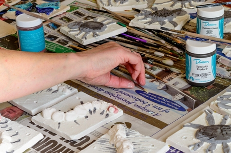 glazing: WREXHAM, UNITED KINGDOM - MARCH 14, 2016: Ceramic mini beasts tiles during the glazing process. Part of a workshop project.