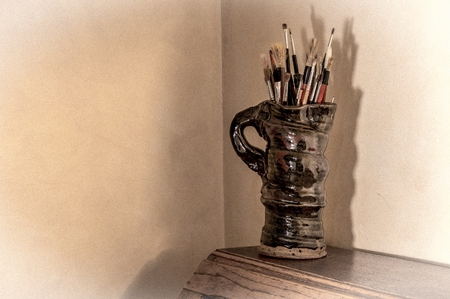 vignetting: Artists paint brushes in pottery jug. Muted tones with added grain and vignetting effects.