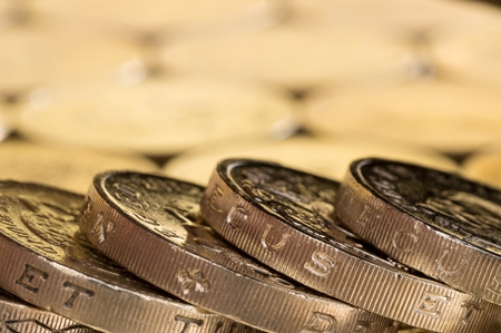 money pound: British money, pound coins spread out in a fallen stack. Stock Photo