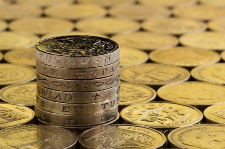 British money, pound coins in a neat stack on a background of more money.