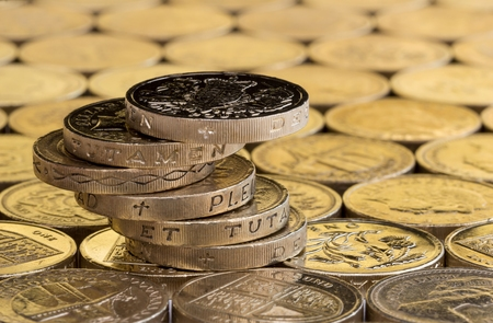 money pound: British money, pound coins balanced in a precarious stack on a background of more money. Stock Photo