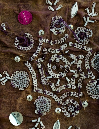 opalescent: Close up detail of vintage sari fabric with embellishments. Grungy disc beads. Stock Photo