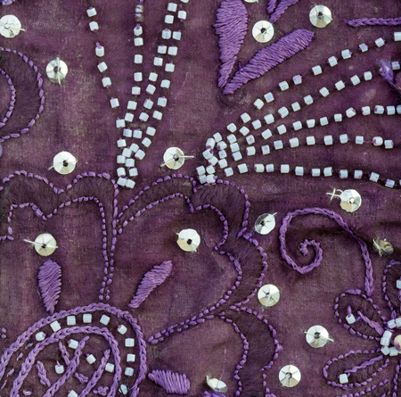 opalescent: Close up detail of vintage sari fabric with embellishments. Purple background.