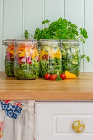 snack food: Prepared salad in glass storage jars on a kitchen work surface. Vertical.