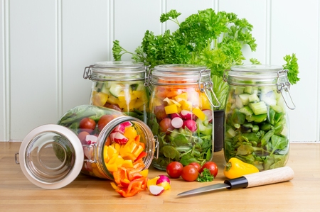 tipped: Prepared salad in glass storage jars. One jar tipped on side spilling contents.