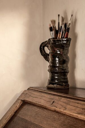 Artists paint brushes in pottery jug. Muted tones. Copy space