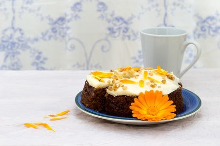 Carrot and marigold cake with butter cream topping, ready to eat for an afternoon snack. Stock Photo