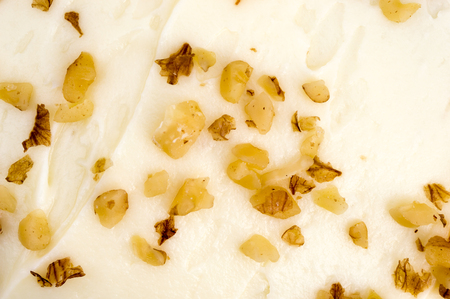 cake topping: Mouth watering icing and walnut cake topping. Close up, background.
