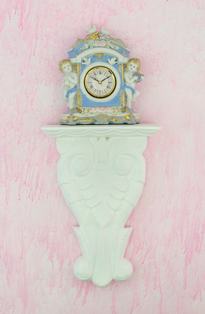 cherubs: Pretty blue vintage porcelain clock with cherubs and doves on a carved white shelf against a pink background. Feminine shabby chic style. Vertical.