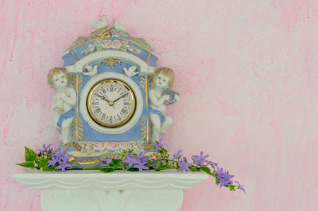 Romantic porcelain clock with cherubs and doves on a white shelf with Campanula flowers against a pink background. Elegant style. Copy space.