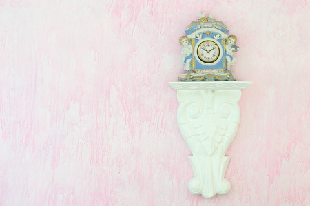 cherubs: Pretty blue vintage porcelain clock with cherubs and doves on a carved white shelf against a pink background. Feminine shabby chic style. Copy space. Stock Photo