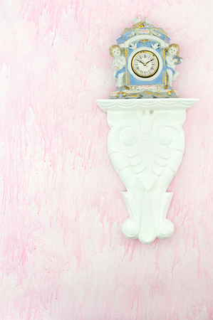 Vintage porcelain clock with cherubs and doves on a carved white shelf against a pink background. Feminine shabby chic style. Copy space.