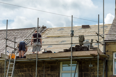 slate roof: WREXHAM, WALES, UNITED KINGDOM - AUGUST 05, 2016: Restoration of decorative slate roof on a residential terraced house in North Wales. With workmen.