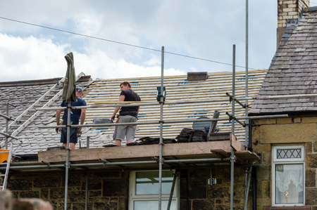 slate roof: WREXHAM, WALES, UNITED KINGDOM - AUGUST 05, 2016: Restoration of decorative slate roof on a residential terraced house in North Wales. With two workmen.