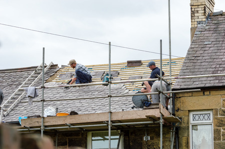 slate roof: WREXHAM, WALES, UNITED KINGDOM - AUGUST 10, 2016: Restoration of decorative slate roof on a residential terraced house in North Wales. With three workmen.