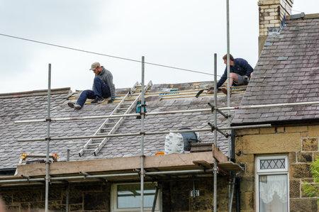 Wrexham, Wales, Verenigd Koninkrijk - 11 augustus 2016: Restauratie van decoratieve leien dak op een residentiële rijtjeshuis in Noord-Wales. Met twee geschoolde dakdekkers. Stockfoto - 64265376