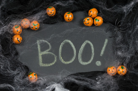 cobwebs: Boo! Written in chalk on slate framed with Halloween candy Jack-o-lanterns, spider and spooky cobwebs. Stock Photo