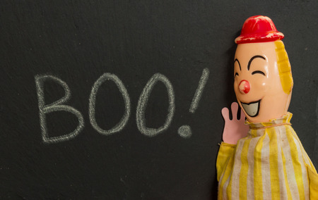 appears: Boo! Chalk text on slate with creepy vintage toy clown. Clown appears to be very happy to have scared someone.