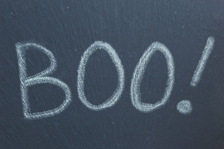 Boo! Chalk text written on slate. Ghostly Halloween word of shock and surprise.