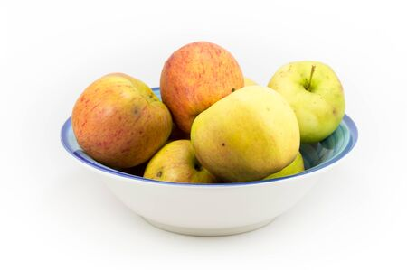 grouped: Windfall apples collected during the autumn season, grouped in a bowl on a white background.