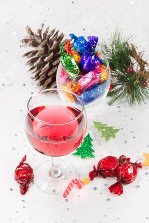 december 25: Festive Christmas party celebrations with glass of wine and wrapped chocolate candy sweets. Treats to enjoy the merry holiday season. On a snowy white background.