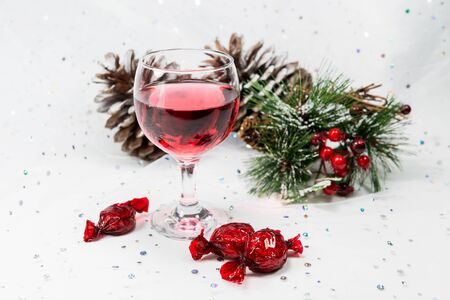 pinecones: Luxury red wine and chocolates among pinecones, sprigs and berries in a chic white snowy Christmas scene.