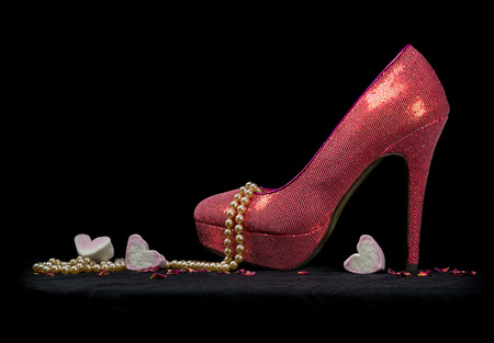 One glamorous pink high heel party shoe with a pearl necklace, candy hearts and dried rose petals on a black background in a pool of light. Love and Saint Valentine's day concept. Copy space