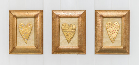 triptych: Gold hearts in frames on a white wooden background. Hand crafted shabby chic triptych for a beautiful home. Love, romance, homely, valentine concept.