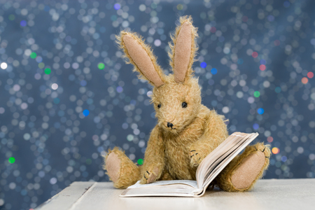 Cute toy rabbit with long ears reading a book. Blue bokeh background. Storytime, child's reading concept.