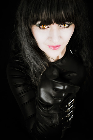 Attractive mature woman pointing finger with gloved hand, wearing black and with amber cats eyes. With a black background. Manipulated effects for reprimand from a cougar concept, Stock Photo