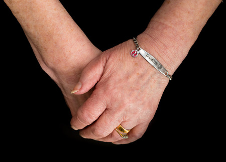 Elderly womans hands wearing a medical alert bracelet for diabetes. Close up on a black background.