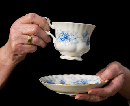 Teacup and saucer held in an old woman's hands about to take a sip of tea. Black background.